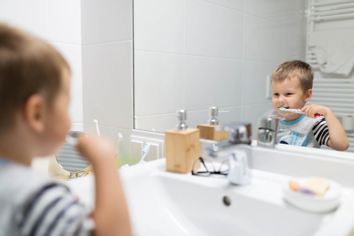 Adorable child brushing his teeth