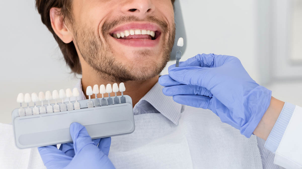 Dentist applying sample from tooth scale to smiling man teeth