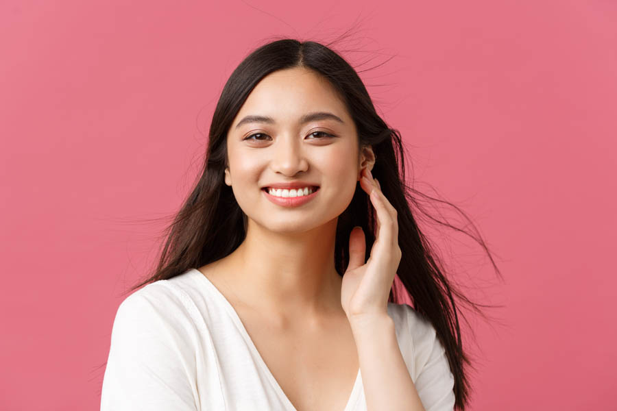 Beauty salon, haircare and skincare products advertisement concept. Close-up of beautiful young asian woman smiling as wind softly blowing at haircut, standing pink background